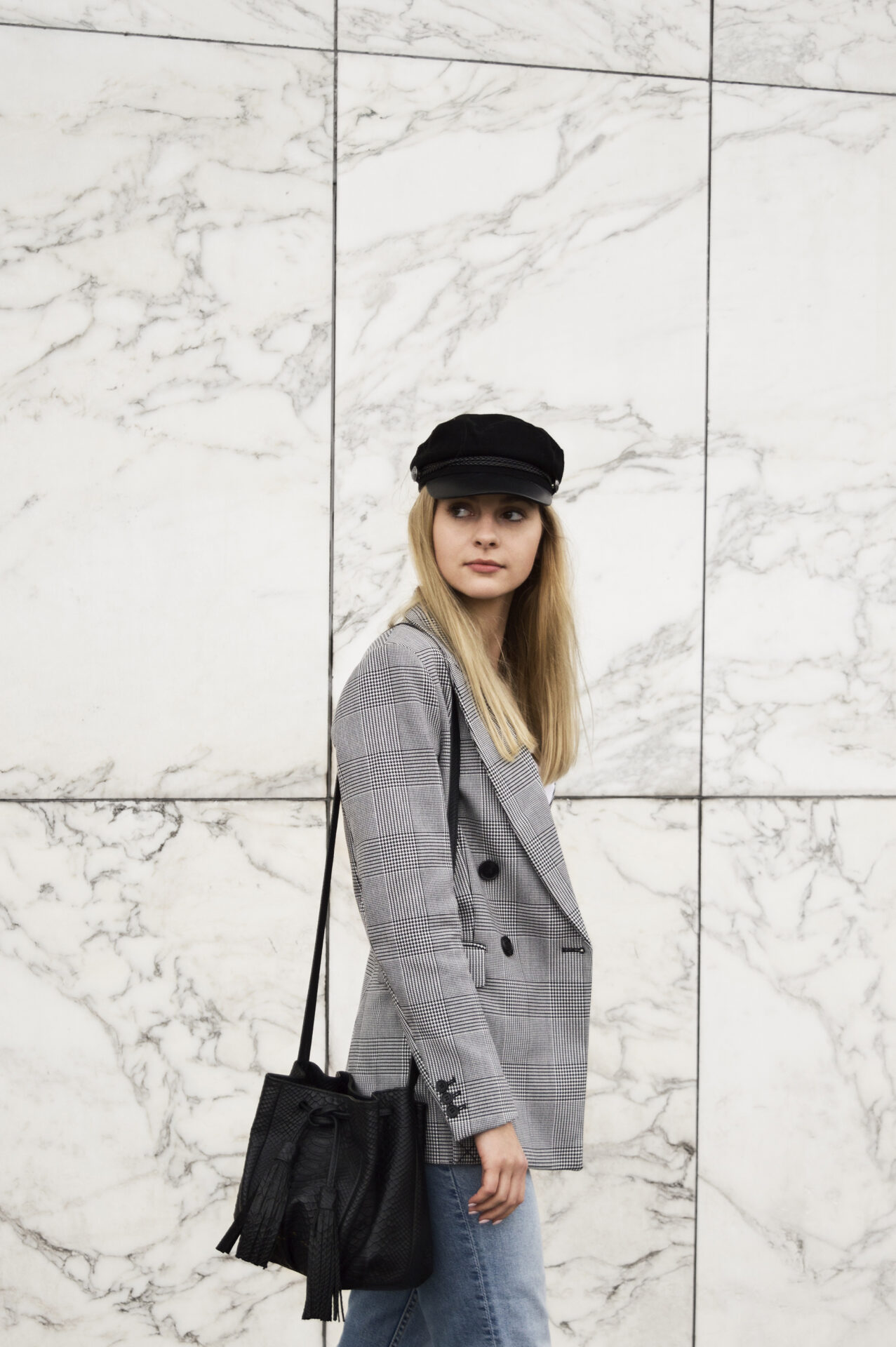 Girl in checked blazer bakerboyhat and blue jeans