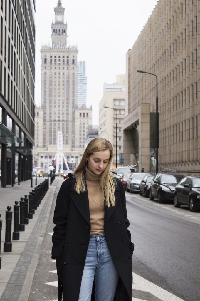 Girl on the street with navy blue H&M coat, blue jeans and camel turtleneck