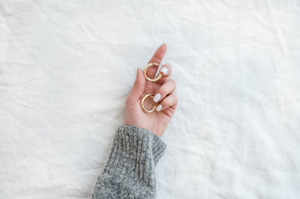 Gold earrings and grey sweater